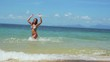 Joyful young woman in bikini running along the exotic beach swimming in the sea on sunny summer day. slow motion. 1920x1080