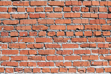 Wall Of Red And Cracked Bricks. Masonry Is Uneven. The Wall Is Covered Or Stained With Cement Mortar. Laying With Alternation. Many Layers. Background, Backdrop Or Wallpaper.