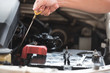 Man hand pulling oil gauge stick up for checking level of motor oil lubricant in the engine, car maintenance service concept.