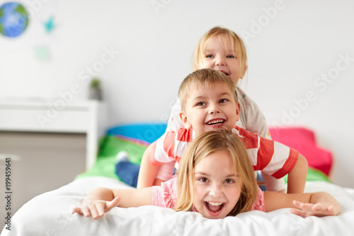 Valokuva  childhood, leisure and family concept - happy little kids having fun in bed at h
