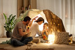 Leinwandbild Motiv hygge and people concept - father with torch light telling scary stories to his daughter and wife, family having fun in kids tent at night at home