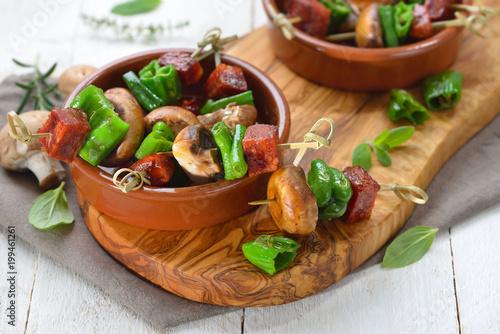 Foto auf AluDibond Bar Spanische Pinchos: Brat-Spießchen mit Chorizo-Salami, Pimientos de Padron und Champignons – Spanish snack: Skewer with fried chorizo sausage, pimentos and mushrooms