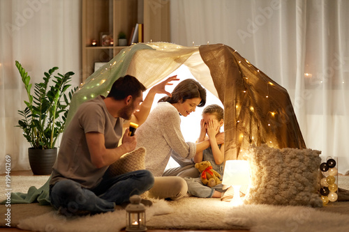 Other hygge and people concept - father with torch light telling scary stories to his daughter and wife, family having fun in kids tent at night at home