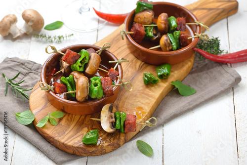 Fotobehang Buffet, Bar Spanische Pinchos: Brat-Spießchen mit Chorizo-Salami, Pimientos de Padron und Champignons – Spanish snack: Skewer with fried chorizo sausage, pimentos and mushrooms