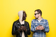 canvas print picture - Two mixed race friends with phone addiction look each other isolated on yellow background. Multiracial friendship
