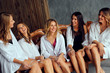 Diverse group of female friends enjoying at a party and laughing. Group Of beautiful women having fun and Sitting on Sofa.Ladies in white clothes
