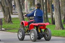 A Boy On A Mechanical ATV Driv...