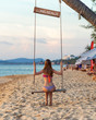 A young woman with a beautiful figure in a bikini swimsuit is sitting on a wooden swing on a sandy Long Beach at sunset on Phu Quoc island in Vietnam. Back view