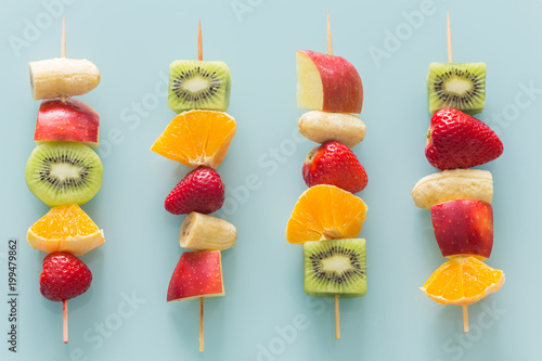 Cuadros en Lienzo fruit skewers the concept of healthy eating / pastel turquoise glass background
