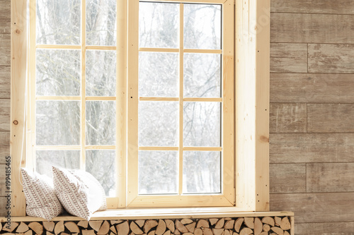 Large windows with wooden frames in a light beige wooden living room ...
