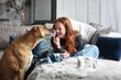 Leinwandbild Motiv Hübsche rothaarige Frau sitzt auf einem Sofa lacht und wird von einem Hund angestupst