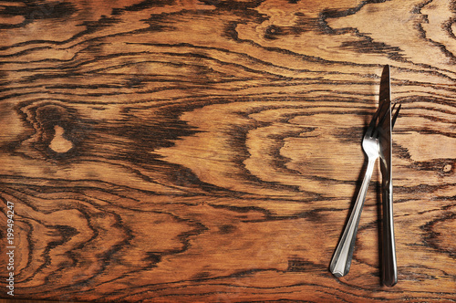 Fototapeta Knife with fork on the wooden background
