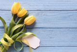 yellow tulip flowers and a blank card on a blue wooden background with copy space, top view from above