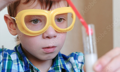 Foto op Aluminium Carnaval Experiments on chemistry at home. Boy look at Chemical reaction with the release of gas in the test tube in the boy,s hands.