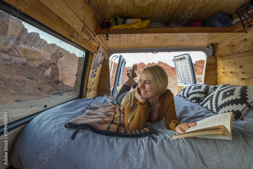 Smiling woman holding book while looking through window in van