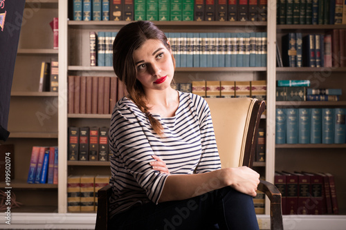 Fotografía  Young caucasian woman dressed in mid century casual fashion poses in a library