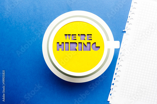 Fotografía  We are hiring concept. Yellow paper cup on blue background.