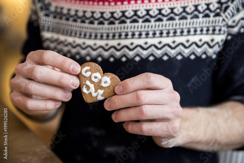 Young man holding gingerbread cookie