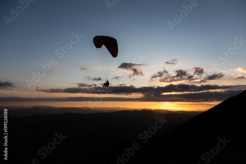 Foto op Canvas Luchtsport Beautiful shot of a paraglider silhouette flying over Monte Cucco (Umbria, Italy) with sunset on the background, with beautiful colors and dark tones