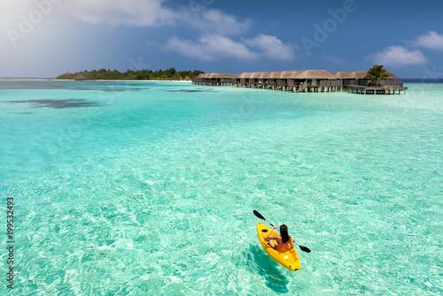 Sportliche Frau im Kajak paddelt über das türkise, tropische Wasser der Malediven