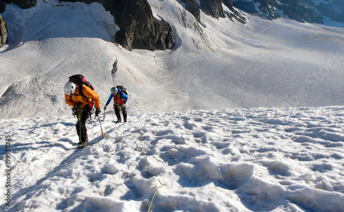 Foto op Plexiglas Alpinisme mountain guide and client heading up a glacier towards a high alpine summit on a beautiful summer morning
