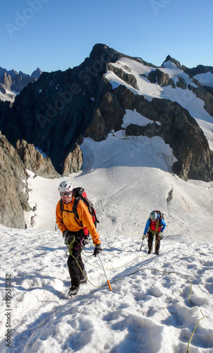 Deurstickers Alpinisme mountain guide and client heading up a glacier towards a high alpine summit on a beautiful summer morning