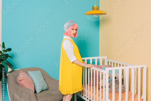 Canvas Print retro styled pregnant pin up woman with pink hair standing near wooden crib in c
