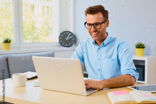 Poster  Happy self employed man working on laptop