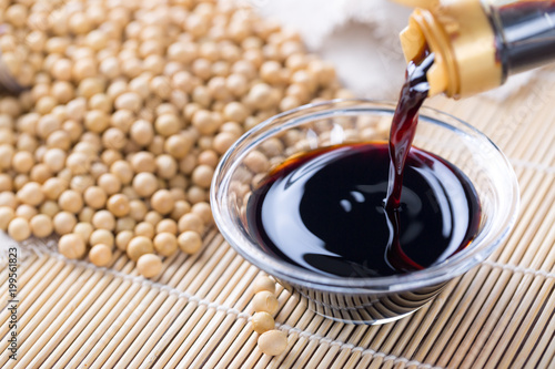 Close up of pouring soy sauce in glass bowl