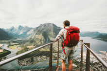Adventurer Man With Red Backpack Enjoying Mountains Scenery Travel Lifestyle Adventure Vacations Traveler Standing Alone On Rampestreken Viewpoint In Norway