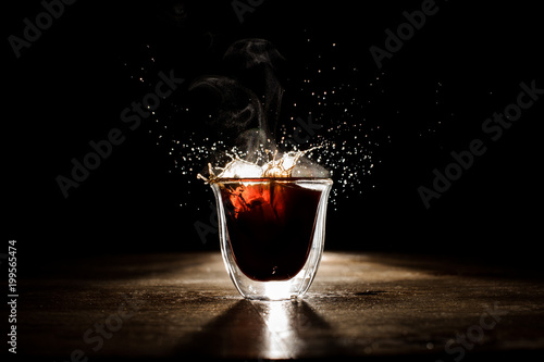 Fotografie, Obraz  Splash of the hot coffee from the transparent glass on the dark background