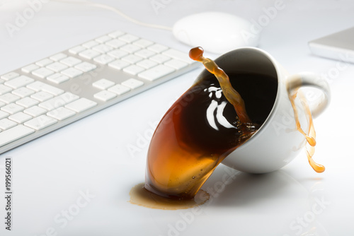 Valokuva  Falling and spilling of a cup of coffee on top of a desk with a computer