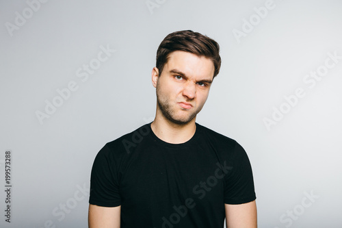 Valokuva  Man disgust while standing against grey background.