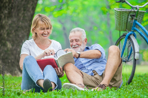 Fotografie, Obraz  Happy elderly couple with smiling face enjoying together, reading a book with magnifying glass in the park, spending time and relaxing time concept