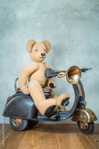 Foto op Canvas Scooter Teddy Bear sitting on old black retro toy scooter with classic klaxon in front concrete textured wall background. Vintage style filtered photo