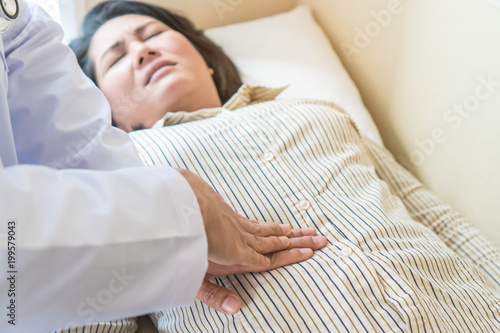 Photo Doctor examining stomach of woman patient and pressing hands on her belly