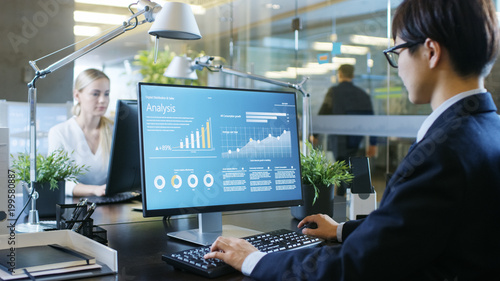 Fotografie, Obraz  In the Office Businessman works at His Desk, He's Using Personal Computer with Statistical Information Showing on It's Screen