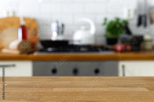 Empty wood counter in front of out of focus home kitchen background.