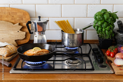 Fotografija Pan fried salmon fillet and spaghetti on a gas stove in traditional home kitchen