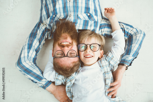 Obraz Top view of cute little boy and his handsome young beard dad, both in eyeglasses, smiling while lying with hands behind head on white floor. - fototapety do salonu