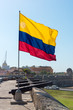 Colombian flag waving on the walls of Cartagena with row of cannon from the colonial era. Colombia