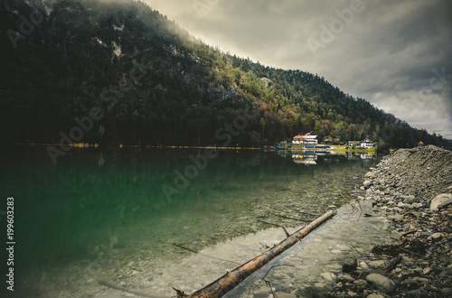 Beautiful lake (Saalach river) in German and Austrian Alps with big mountains and sunlight on background in winter Misty green lake with clear and cold water with fog above, and cloudy sky.