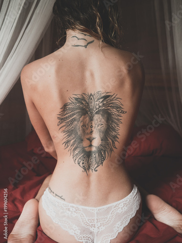 Naked Back With The Tattoo Of A Lion Of A Young Woman Sitting On A