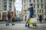 Motion blurred shoppers on busy high street carrying shopping bags