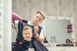 Little boy getting his hair styled at hairdresser's.