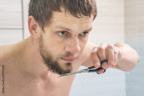 Fotografia, Obraz  The guy is a scissors with a beard on his chin