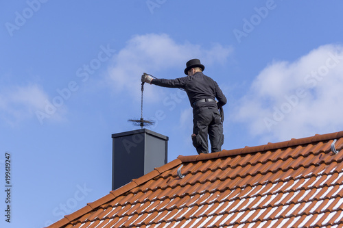 Fotografía Chimney sweep cleaning a chimney standing on the house roof, lowering equipment