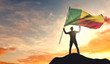 Benin flag being waved by a man celebrating success at the top of a mountain. 3D Rendering