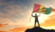 Guinea flag being waved by a man celebrating success at the top of a mountain. 3D Rendering