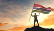 Gambia flag being waved by a man celebrating success at the top of a mountain. 3D Rendering